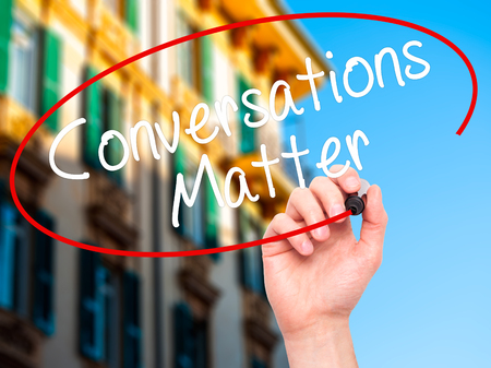 business matter: Man Hand writing Conversations Matter with black marker on visual screen. Isolated on city. Business, technology, internet concept. Stock Image Stock Photo