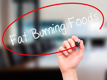 fat burning: Man Hand writing Fat Burning Foods with black marker on visual screen. Isolated on office. Business, technology, internet concept. Stock Photo