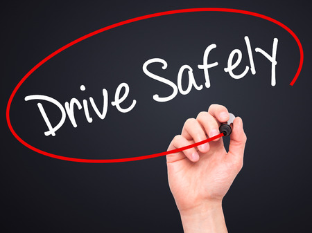 drive safely: Man Hand writing  Drive Safely with black marker on visual screen. Isolated on black. Business, technology, internet concept. Stock Photo Stock Photo