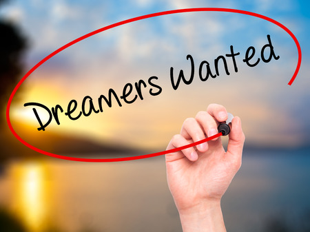innovator: Man Hand writing Dreamers Wanted  with black marker on visual screen. Isolated on background. Business, technology, internet concept. Stock Photo