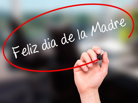 dia de la madre: Man Hand writing Feliz dia de la Madre (Happy Mothers Day in Spanish)  with black marker on visual screen. Isolated on office. Business, technology, internet concept. Stock Photo