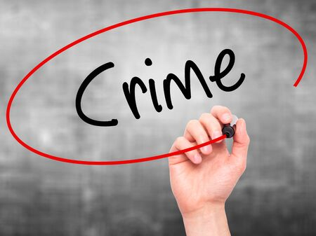 theft prevention: Man Hand writing Crime with black marker on visual screen. Isolated on background. Business, technology, internet concept. Stock Photo