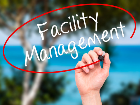 dwell house: Man Hand writing Facility Management with black marker on visual screen. Isolated on nature. Business, technology, internet concept. Stock Photo Stock Photo