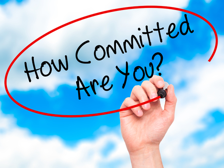 committed: Man Hand writing How Committed Are You? with black marker on visual screen. Isolated on sky. Business, technology, internet concept. Stock Photo