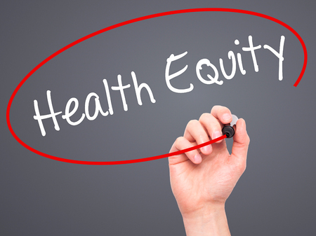 health equity: Man Hand writing Health Equityt with black marker on visual screen. Isolated on grey. Business, technology, internet concept. Stock Photo