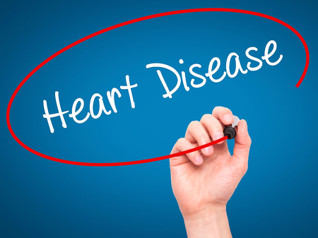 arrhythmias: Man Hand writing Heart Disease with black marker on visual screen. Isolated on blue. Business, technology, internet concept. Stock Photo Stock Photo