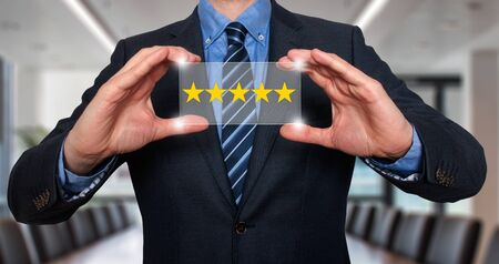 hotel reviews: Businessman holding five star rating. Office - Stock Image