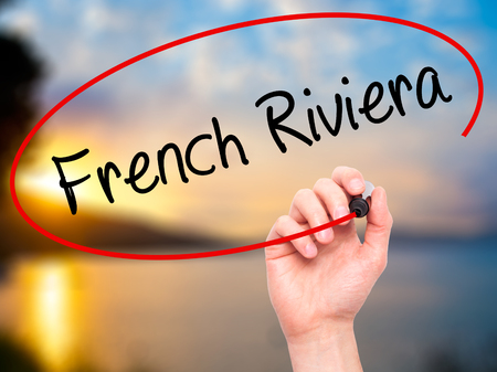 Man Hand writing French Riviera with black marker on visual screen. Isolated on background. Business, technology, internet concept. Stock Photo