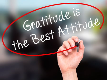 positiveness: Man Hand writing Gratitude is the Best Attitude with black marker on visual screen. Isolated on office. Business, technology, internet concept. Stock Photo