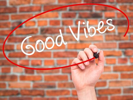 vibrations: Man Hand writing Good Vibes with black marker on visual screen. Isolated on bricks. Business, technology, internet concept. Stock Photo Stock Photo