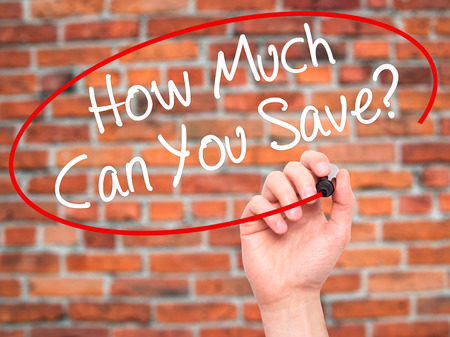 Man Hand writing How Much Can You Save? with black marker on visual screen. Isolated on bricks. Business, technology, internet concept. Stock Photo