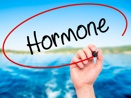 testosterone: Man Hand writing Hormone with black marker on visual screen. Isolated on background. Business, technology, internet concept. Stock Photo