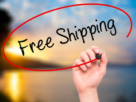 writing on screen: Man Hand writing Free Shipping with black marker on visual screen. Isolated on nature. Business, technology, internet concept. Stock Photo