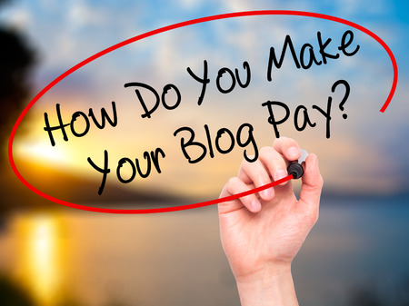 adwords: Man Hand writing How Do You Make Your Blog Pay? with black marker on visual screen. Isolated on nature. Business, technology, internet concept. Stock Photo