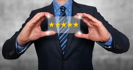 five star: Businessman holding five star rating. Grey - Stock Image