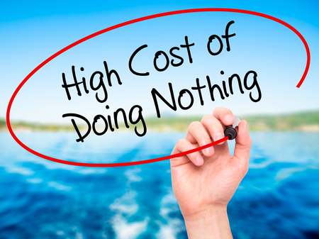high cost: Man Hand writing High Cost of Doing Nothing with black marker on visual screen. Isolated on nature. Business, technology, internet concept. Stock Photo