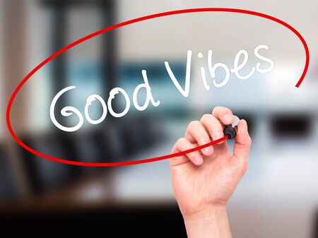 philosophy of music: Man Hand writing Good Vibes with black marker on visual screen. Isolated on office. Business, technology, internet concept. Stock Photo