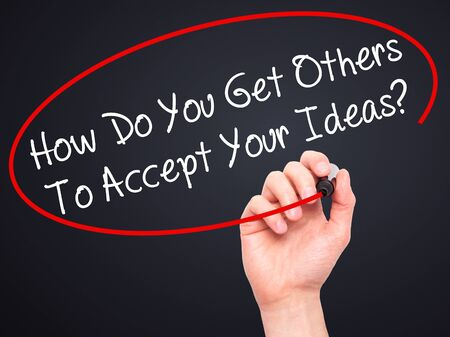 persuasiveness: Man Hand writing How Do You Get Others To Accept Your Ideas? with black marker on visual screen. Isolated on black. Business, technology, internet concept. Stock Photo Stock Photo