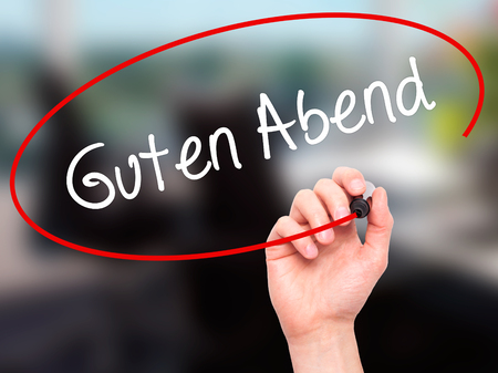 good evening: Man Hand writing Guten Abend  (Good Evening in German) with black marker on visual screen. Isolated on background. Business, technology, internet concept. Stock Photo