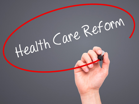 hmo: Man Hand writing Health Care Reform with black marker on visual screen. Isolated on grey. Business, technology, internet concept.