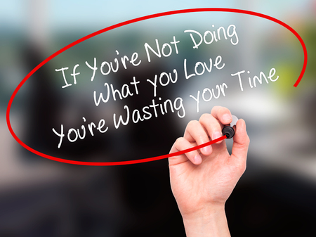 what if: Man Hand writing If Youre Not Doing What you Love Youre Wasting your Time with black marker on visual screen. Isolated on office. Business, technology, internet concept. Stock Photo