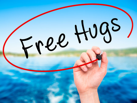 nature photo: Man Hand writing Free Hugs with black marker on visual screen. Isolated on nature. Business, technology, internet concept. Stock Photo