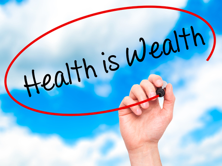 career life: Man Hand writing Health is Wealth with black marker on visual screen. Isolated on sky. Business, technology, internet concept. Stock Photo