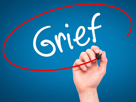 lamentation: Man Hand writing Grief with black marker on visual screen. Isolated on background. Business, technology, internet concept. Stock Photo