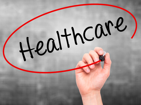 mandate: Man Hand writing Healthcare with black marker on visual screen. Isolated on grey. Business, technology, internet concept. Stock Photo