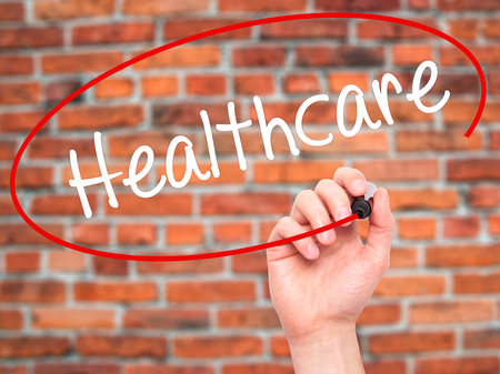 mandated: Man Hand writing Healthcare with black marker on visual screen. Isolated on bricks. Business, technology, internet concept. Stock Photo