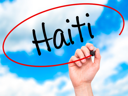 port au prince: Man Hand writing Haiti with black marker on visual screen. Isolated on sky. Business, technology, internet concept. Stock Photo Stock Photo