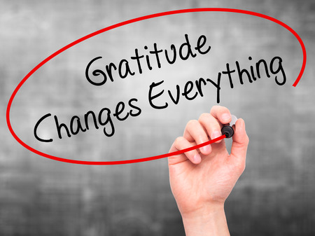 thankfulness: Man Hand writing Gratitude Changes Everything with black marker on visual screen. Isolated on grey. Business, technology, internet concept. Stock Photo Stock Photo