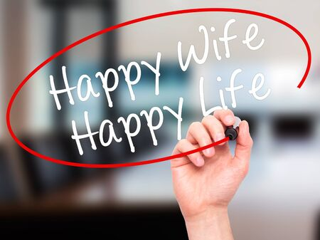 wedlock: Man Hand writing Happy Wife Happy Life with black marker on visual screen. Isolated on office. Business, technology, internet concept. Stock Photo