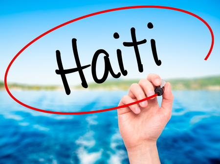 port au prince: Man Hand writing Haiti with black marker on visual screen. Isolated on nature. Business, technology, internet concept. Stock Photo