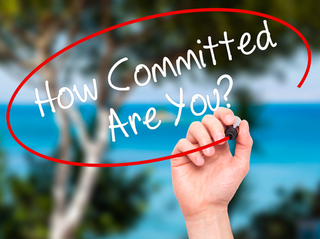 committed: Man Hand writing How Committed Are You? with black marker on visual screen. Isolated on nature. Business, technology, internet concept. Stock Photo