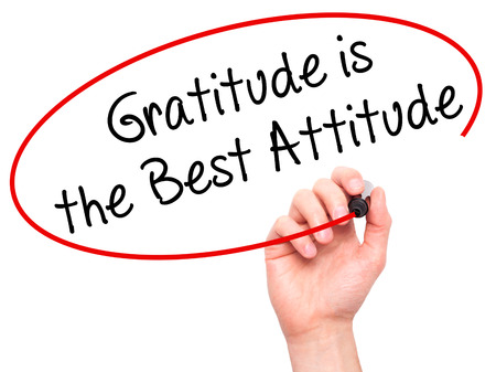 positiveness: Man Hand writing Gratitude is the Best Attitude with black marker on visual screen. Isolated on white. Business, technology, internet concept. Stock Photo