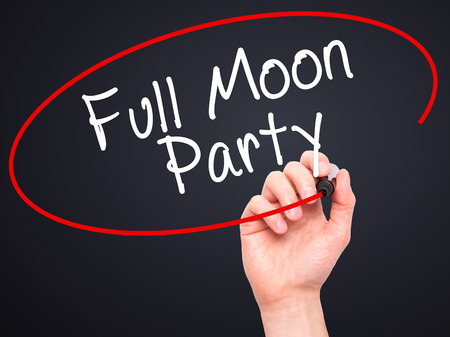 rin: Man Hand writing Full Moon Party with black marker on visual screen. Isolated on black. Business, technology, internet concept. Stock Image Stock Photo