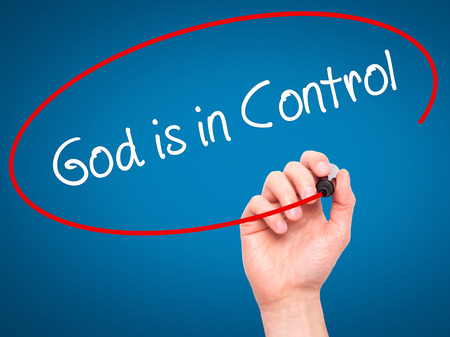 sanctification: Man Hand writing God is in Control with black marker on visual screen. Isolated on blue. Business, technology, internet concept. Stock Photo