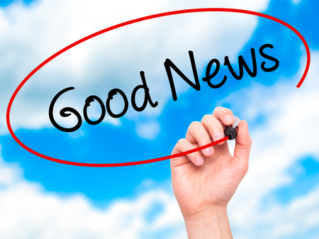 annoucement: Man Hand writing Good News with black marker on visual screen. Isolated on sky. Business, technology, internet concept.