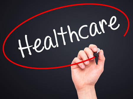 mandated: Man Hand writing Healthcare with black marker on visual screen. Isolated on black. Business, technology, internet concept. Stock Photo
