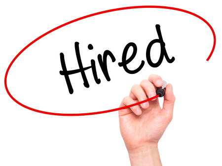 recruit help: Man Hand writing Hired with black marker on visual screen. Isolated on background. Business, technology, internet concept. Stock Photo