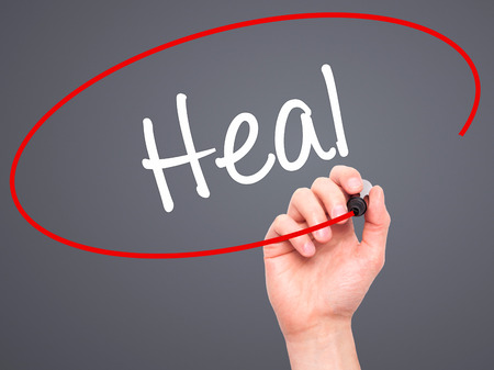 SELF HEALING: Man Hand writing  Heal  with black marker on visual screen. Isolated on background. Business, technology, internet concept. Stock Photo Stock Photo