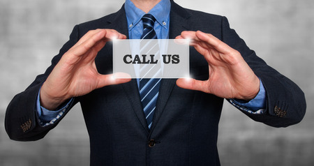 smartness: Business man holding Call Us card. Grey - Stock Photo