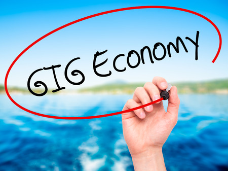 gig: Man Hand writing GIG Economy with black marker on visual screen. Isolated on background. Business, technology, internet concept. Stock Photo