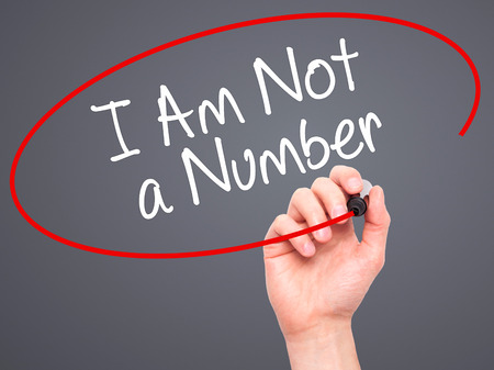 consumer rights: Man Hand writing I Am Not a Number with black marker on visual screen. Isolated on background. Business, technology, internet concept. Stock Photo Stock Photo