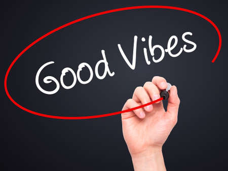 positivism: Man Hand writing Good Vibes with black marker on visual screen. Isolated on black. Business, technology, internet concept. Stock Photo Stock Photo