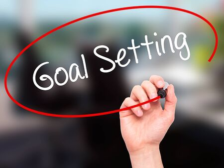 reachable: Man Hand writing Goal Setting  with black marker on visual screen. Isolated on office. Business, technology, internet concept. Stock Photo
