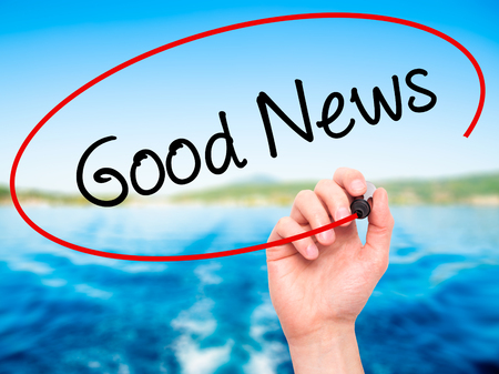 annoucement: Man Hand writing Good News with black marker on visual screen. Isolated on nature. Business, technology, internet concept.