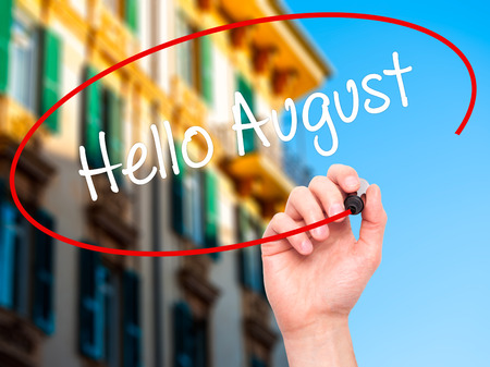 hi back: Man Hand writing Hello August with black marker on visual screen. Isolated on city. Business, technology, internet concept. Stock Photo