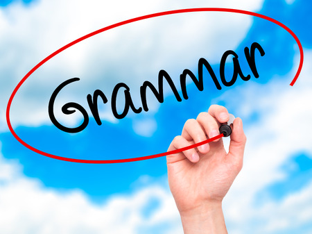 verb: Man Hand writing Grammar with black marker on visual screen. Isolated on background. Business, technology, internet concept. Stock Photo Stock Photo